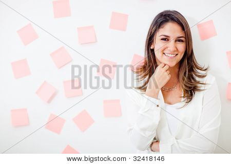 Multitask businesswoman with post-its and smiling