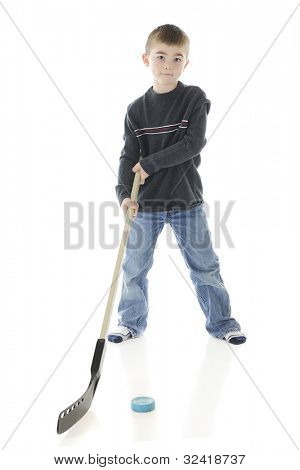 A young elementary boy posing with his hockey stick and puck.  On a white background.