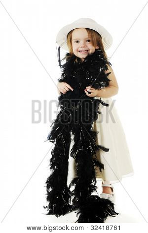 A beautiful preschooler dressed up in white and wrapped in a feathery black boa.  On a white background.