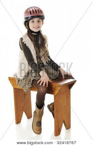 ein ziemlich elementaren Mädchen tragen ihr Pferd Reiten, Helm und Stiefel, gebietsübergreifenden einer rustikalen Holz Bank.