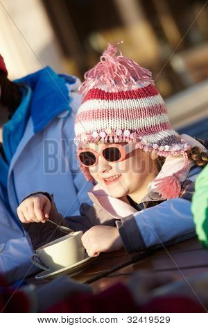 Young Girl Enjoying Hot Drink In Cafe At Ski Resort