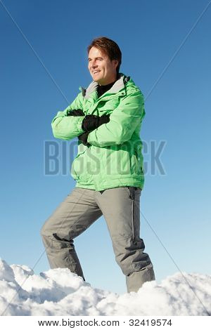 Man Standing In Snow Wearing Warm Clothes On Ski Holiday In Mountains