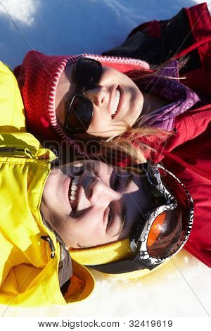 Overhead View Of Mother And Teenage Son Lying In Snow On Ski Holiday In Mountains