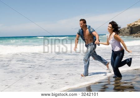 Couple Running By The Seaside