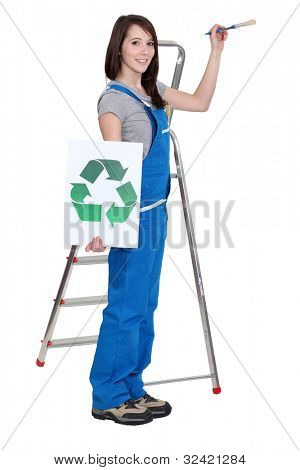 lovely brunet painter in blue dungarees holding brush and recycling logo