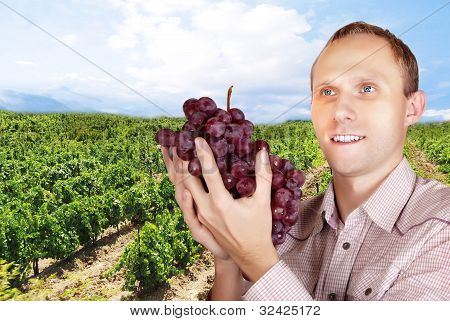 Man With A Bunch Of Grapes On The Vineyard Background