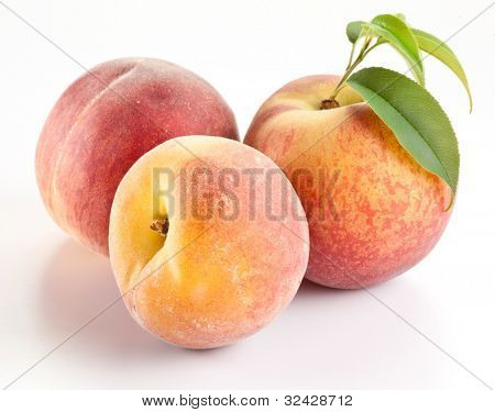 Three ripe peach with leaves on white background.