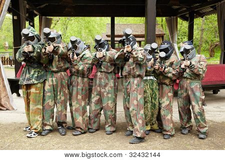 Boys dressed in camouflage stand in a line and aiming with paintball guns on a paintball base