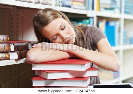 Young tired pretty woman sleeping resting on books pile in a library at self-education
