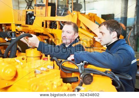 adult experienced industrial workers during heavy industry machinery assembling on production line manufacturing workshop