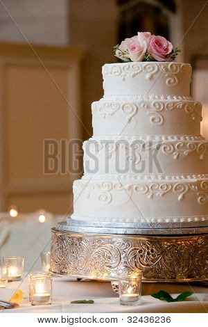 a multi level white wedding cake on a silver base and pink flowers on top