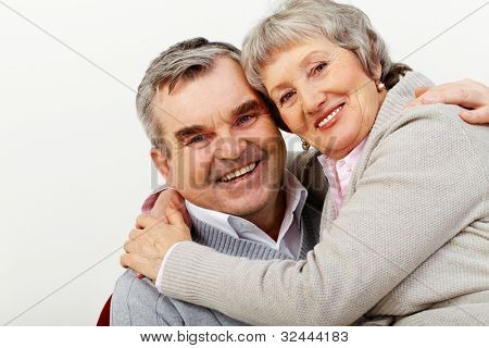 Portrait of a mature couple happily hugging and looking at cam