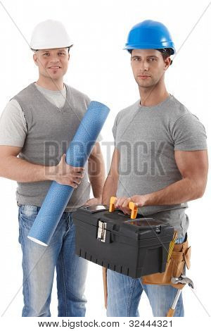 Athletic contractor standing holding toolset, engineer guy holding floor plan, wearing hardhat, smiling at camera, isolated on white.