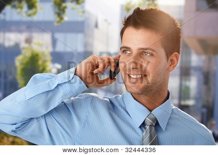Outdoor spring portrait of smiling businessman speaking on cellphone in front of office building.