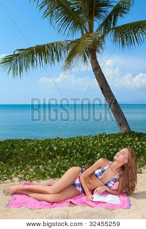 Beautiful blonde woman relaxing on a pink towel under a palm tree reading on a tropical beach with ocean backdrop