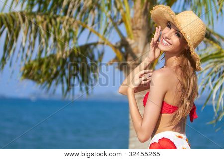 Joyful girl in red bikini posing at the tropical beach