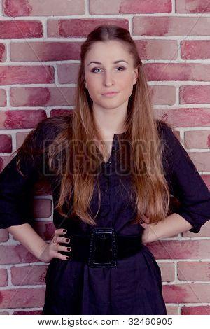 Beautiful blond woman on brick wall