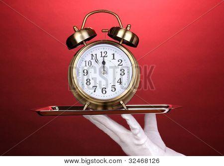 Mão na luva, segurando a bandeja de prata com despertador em fundo vermelho