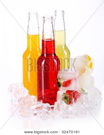 Bottles with colorful cocktail and ice over white background