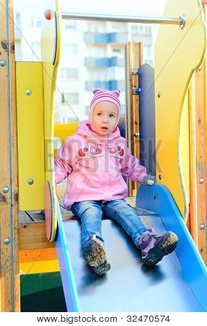 Child Girl Sitting On Slide In Playground.