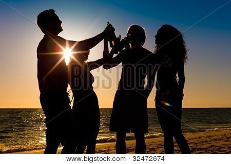 People (two couples) on the beach having a party, drinking and having a lot of fun in the sunset (only silhouette seen, people having bottles in their hands with the sun shining through)