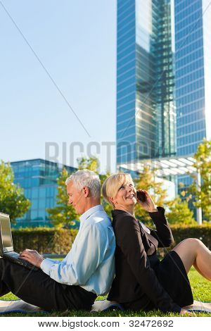 Business people working outdoors on a meadow - he is working with laptop, she is calling someone on phone