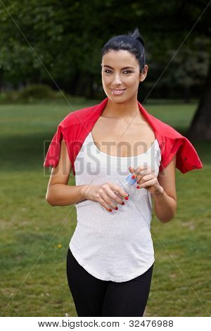 Attractive young woman training in citypark, smiling.
