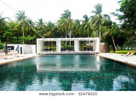 Tropical swimming pool with sunbeds in Thailand