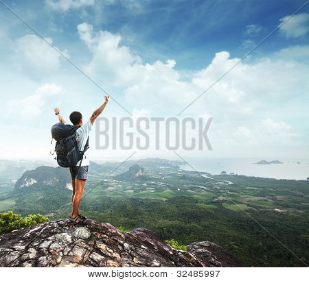 Young man with backpack standing with raised hands on top of a mountain and enjoying valley view