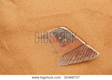 ancient Anasazi pottery shard buried in red desert sand
