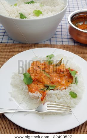 A homemade tomato curry, thickened with coconut and garnished with coriander and curry leaves, served on basmati rice. This is a delicious traditional recipe from Kerala, India.