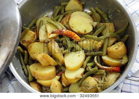 A potato and green bean curry in the saucepan it is cooking in.