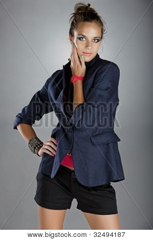 beautiful  young woman with dramatic make-up and green pink manicure wearing shorts, dark navy blue linen jacket and pink neon watch on gray background