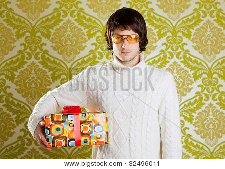 retro hip young man glasses holding  psychedelic gift box on wallpaper