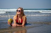Sexy And Young Woman In A Stylish Bikini Swimsuit Holding A Coconut On The Ocean Tropical Paradise S poster