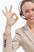 Approbation of a businesswoman with a headset against white background