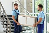 Professional Workers Carrying Cabinet At Stairs In Office. Moving Service poster
