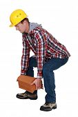 stock photo of shingle  - Tradesman lifting shingles - JPG