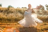 Bride On A Summer Field In White Wedding Dress Rolling And Dancing In Sunset Light. Sun Beams Seen T poster