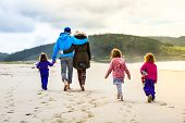 Happy Young Family Is Walking On Sandy Beach And Ocean. happy Family - Father, Mother, Baby Girls Ho poster