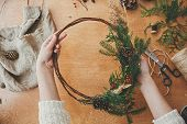 Christmas Wreath Workshop. Hands Holding Fir Branches, Pine Cones, Berries, Thread, Scissors On Wood poster
