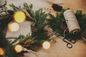 Rustic Christmas Wreath. Fir Branches, Pine Cones, Thread, Berries, Scissors And Golden Lights Bokeh poster