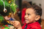 Little Boy Decorating Christmas Tree And Having Fun. poster