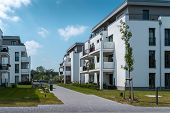 Real Estate Modern Apartments And Penthouses Surrounded By Grassy Areas Blue Sky Green Meadow Expens poster
