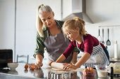 Grandmother and little girl making cookies in kitchen. Happy granddaughter with old grandma using ro poster