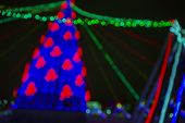 A Background Image Consisting Of A Blurred Image Of A Christmas Tree Decorated With Electric Lights. poster