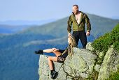 On Edge Of World. Woman Sit Edge Of Cliff High Mountains Landscape Background. Couple Hikers Enjoy V poster