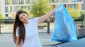 A Woman Smiles And Looks Into The Camera Throws A Bag Of Garbage Into The Tank Near The House. poster