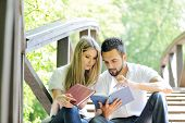 stock photo of reading book  - Beautiful couple reading book outdoors - JPG