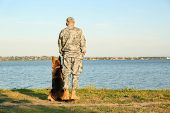 Man In Military Uniform With German Shepherd Dog Outdoors poster